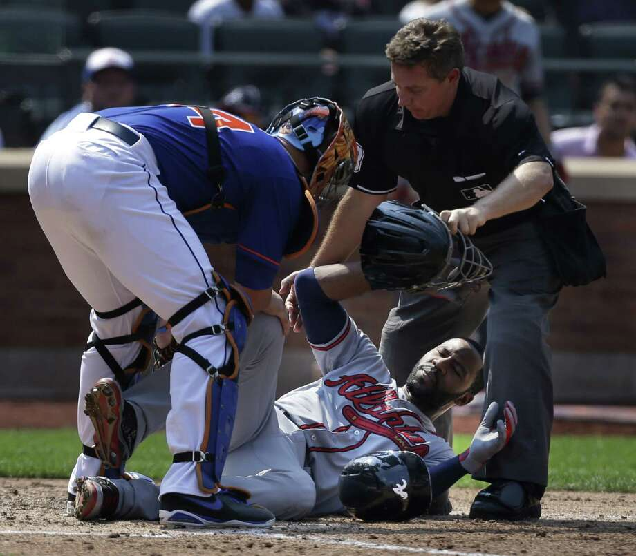 Atlanta Braves' Jason Heyward, center, is helped by New York Mets catcher John Buck, left, and umpire Greg Gibson after being hit by a pitch thrown by New York Mets' Jonathon Niese during the sixth inning of the baseball game at Citi Field Wednesday, Aug. 21, 2013 in New York. (AP Photo/Seth Wenig) ORG XMIT: NYM110 Photo: Seth Wenig / AP