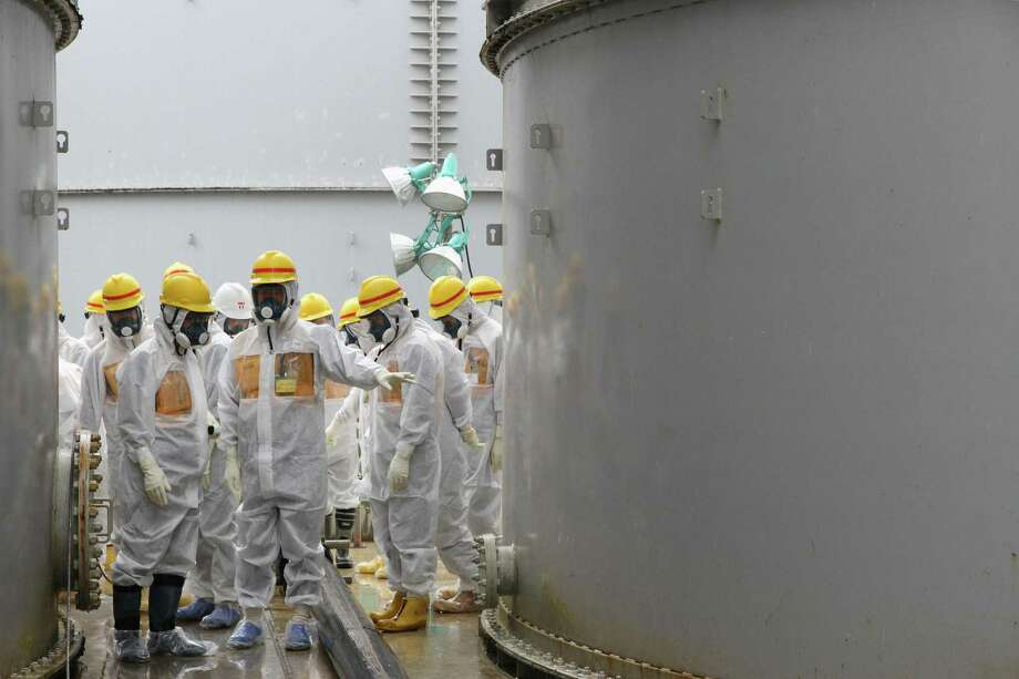 Nuclear Regulation Authority commissioners inspect storage tanks used to contain radioactive water at the Fukushima Daiichi nuclear power plant in northern Japan. Photo: Nuclear Regulation Authority / Associated Press