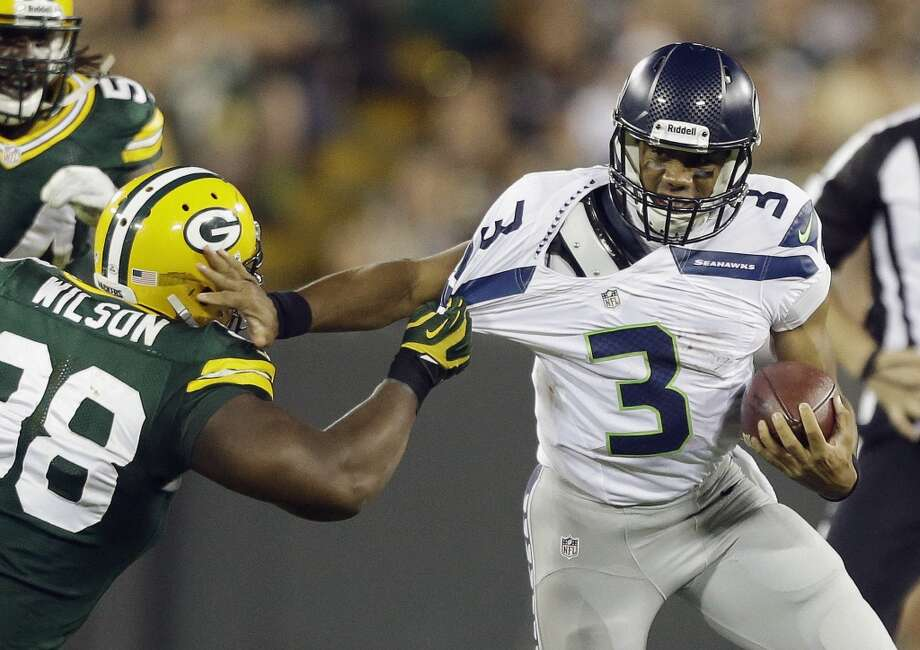 Seattle Seahawks quarterback Russell Wilson tries to get away from Green Bay Packers' C.J. Wilson during the second half of an NFL preseason football game Friday, Aug. 23, 2013, in Green Bay, Wis. (AP Photo/Jeffrey Phelps) Photo: AP