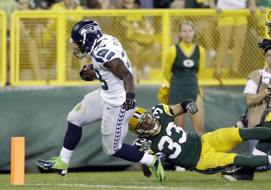 Seattle Seahawks' Christine Michael breaks away from Green Bay Packers' Micah Hyde for a touchdown run during the second half of an NFL preseason football game Friday, Aug. 23, 2013, in Green Bay, Wis. (AP Photo/Jeffrey Phelps) Photo: AP