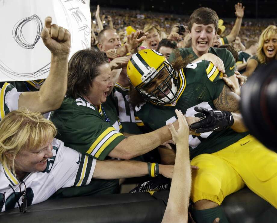 Green Bay Packers' Jonathan Amosa celebrates with fans after a touchdown catch during the second half of an NFL preseason football game against the Seattle Seahawks Friday, Aug. 23, 2013, in Green Bay, Wis. (AP Photo/Morry Gash) Photo: AP