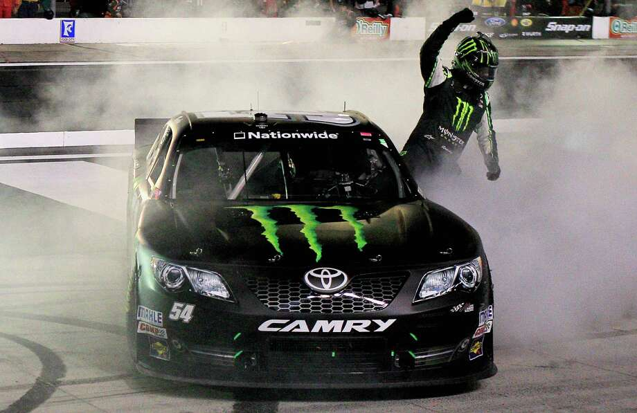 Kyle Busch pumps his fist after his celebratory burnout. Busch added the Nationwide Series win Friday night to his Truck Series victory Wednesday. Photo: Sean Gardner, Stringer / 2013 Getty Images
