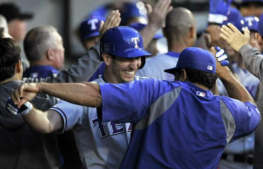 Adam Rosales (center) celebrates his two-run home run with his Texas teammates in the second inning of the Rangers' blowout victory against the White Sox in Chicago. They hit five homers in the game. Photo: Paul Beaty / Associated Press