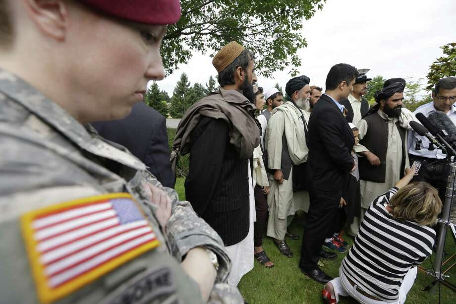 A U.S. soldier looks on as Afghan villagers, some of whom testified earlier, talk with reporters after the sentencing of Staff Sgt. Robert Bales at Joint Base Lewis-McChord, Wash. Photo: Elaine Thompson / Associated Press
