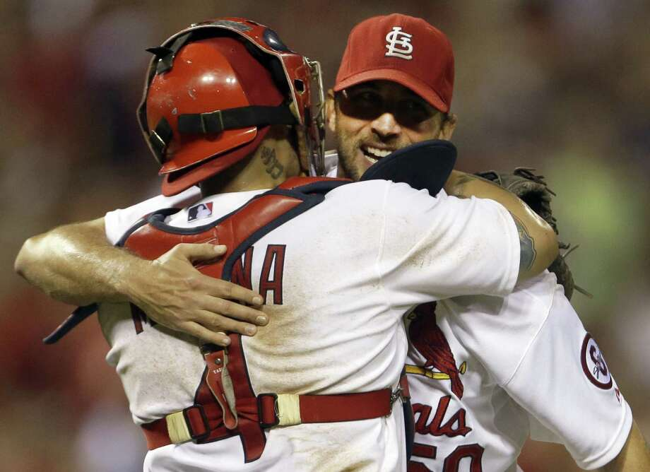 St. Louis pitcher Adam Wainwright (right), who tossed his fifth complete game this season, receives congratulations from catcher Yadier Molina. Photo: Jeff Roberson / Associated Press