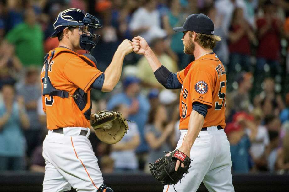 Astros catcher Cody Clark, left, had plenty to celebrate Friday - his first appearance in the majors after 11 seasons in the minors and a 12-4 win over the Blue Jays. Photo: Smiley N. Pool / © 2013  Smiley N. Pool