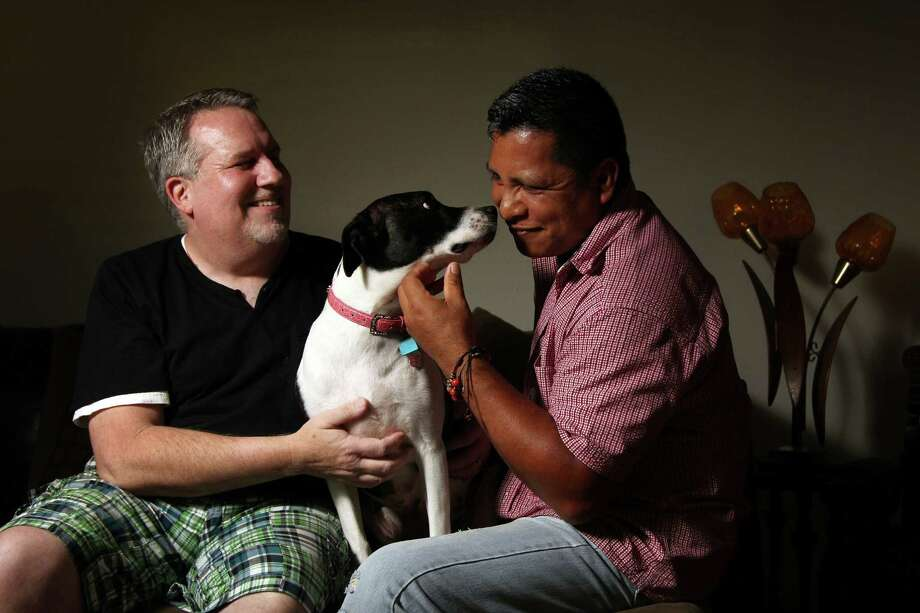 Fred Smith and Isaias Rivas-Guzman, with their new rescue dog, Lucy at their home. Smith and Rivas-Guzman met in 2005 at a church group dinner, and with months, they moved in together. Photo: Mayra Beltran / Houston Chronicle