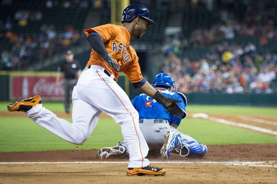 Astros right fielder L.J. Hoes scores on a throwing error by Blue Jays starting pitcher Todd Redmond as catcher J.P. Arencibia takes the late throw to home. Photo: Smiley N. Pool, Houston Chronicle
