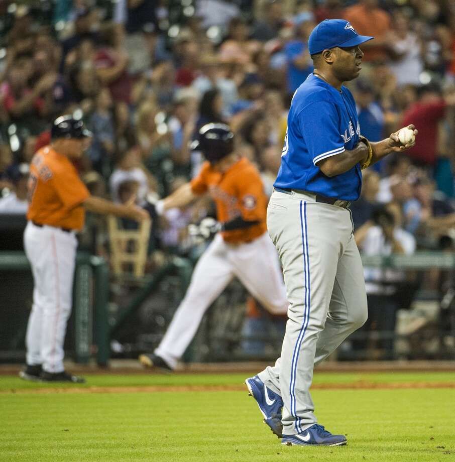 Blue Jays relief pitcher Darren Oliver looks away  as Astros left fielder Robbie Grossman rounds the bases after hitting a home run. Photo: Smiley N. Pool, Houston Chronicle
