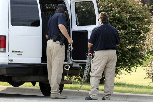 Private security personnel unload shackles before the deliberations continued in the trial of Maj. Nidal Hasan. It wasn't known if the shackles were related to that case. Photo: Jerry Lara / San Antonio Express-News
