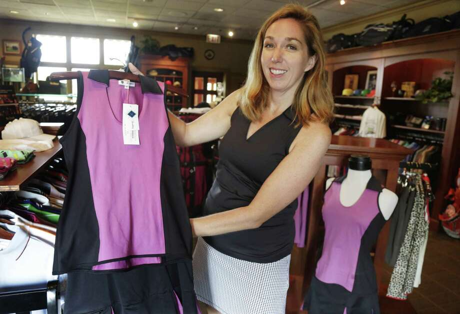 In this Tuesday, Aug. 20, 2013 photo, Kelly Daugherty, co-owner of Smashing Golf & Tennis, poses for a photo with her clothing line in the pro shop at Biltmore Country Club in North Barrington, Ill. The owners of Smashing Golf & Tennis can't take vacations this summer because they're training new sales people for the company's line of active wear for women. They also are getting their spring styles ready and have to be around for last-minute orders, as this is high season for golfers and tennis players. (AP Photo/M. Spencer Green) Photo: M. Spencer Green, STF / AP