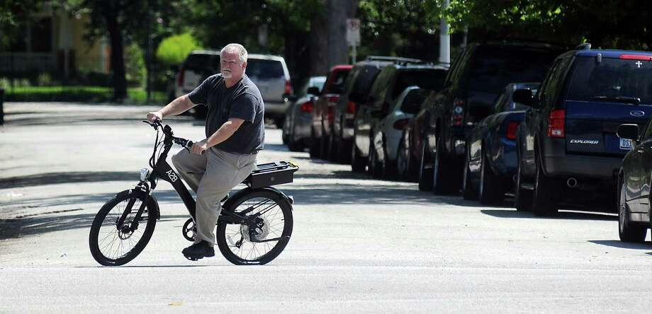 Dennis Humphreys, owner of Revolution E bikes, rides one of the electric bikes for sale at his store on Westheimer. He says people really go for the concept. Photo: Dave Rossman, Freelance / © 2013 Dave Rossman