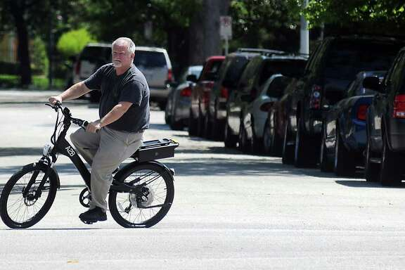 Dennis Humphreys, owner of Revolution E bikes, rides one of the electric bikes for sale at his store on Westheimer. He says people really go for the concept.
