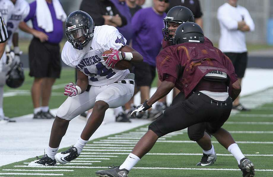 Morton Ranch wide receiver Torrey Thomas tries to maneuver away from George Ranch defenders as the Mavericks scrimmaged George Ranch at Traylor Stadium in Rosenberg on August 23, 2013. Photo by Diana L. Porter Photo: Diana L. Porter / © Diana L. Porter