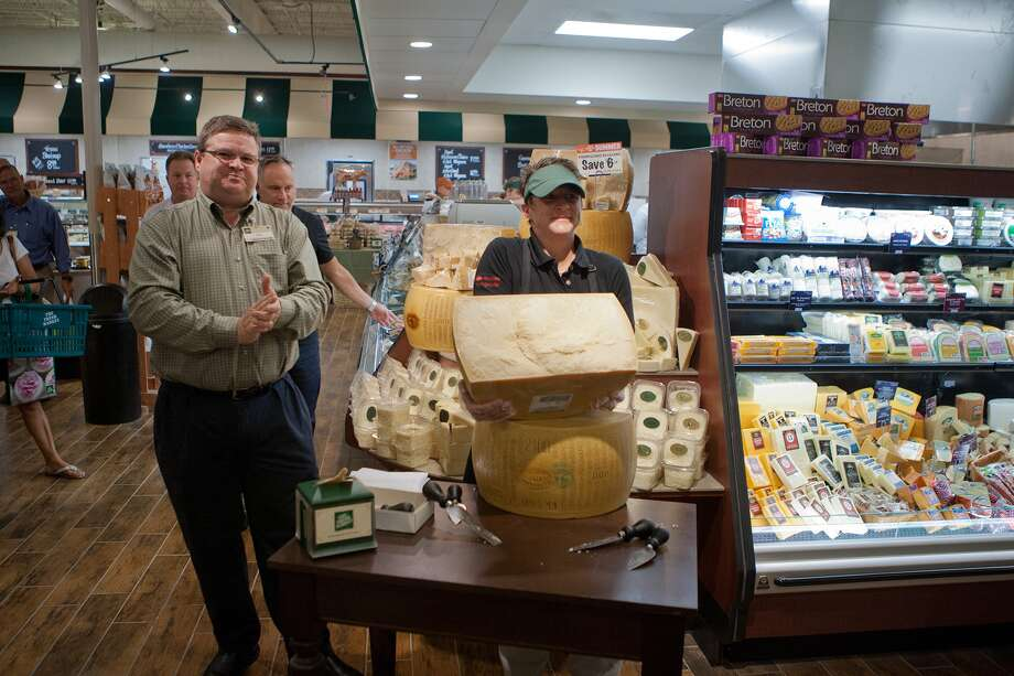 Ken Towery, Zone Vice President of Operations,stands by as Pam Rosencrans (spOK) of Anco Fine Cheese in New Jersey shows off the freshly cracked 84-lb parmesan wheel upon the opening of the new Fresh Market on San Felipe near Post Oak.  Photo: R. Clayton McKee, For The Chronicle / © R. Clayton McKee