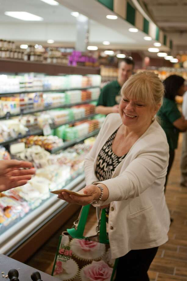 Lynn Rowan goes for a sample of Parmagiana Reggiano cheese at the new Fresh Market on San Felipe near Post Oak.  Photo: R. Clayton McKee, For The Chronicle / © R. Clayton McKee