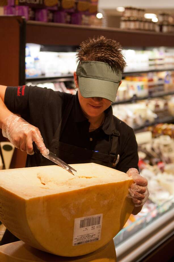 Pam Rosencrans of Anco Fine Cheese cuts samples off the store's opening wheel at the new Fresh Market on San Felipe near Post Oak.  Photo: R. Clayton McKee, For The Chronicle / © R. Clayton McKee