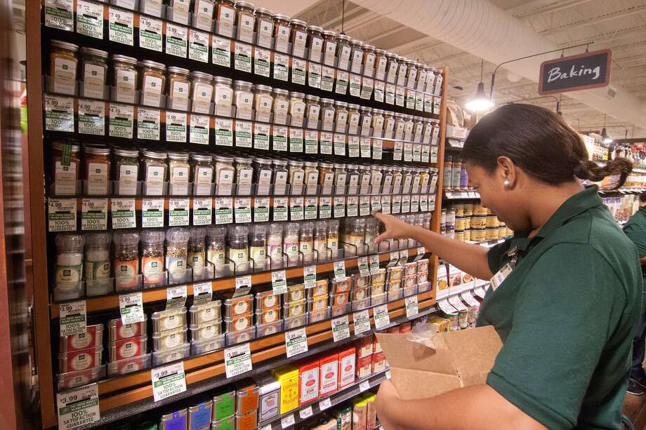 Shalonda Cross restocks the spice jars at the new Fresh Market on San Felipe near Post Oak.  Photo: R. Clayton McKee, For The Chronicle / © R. Clayton McKee