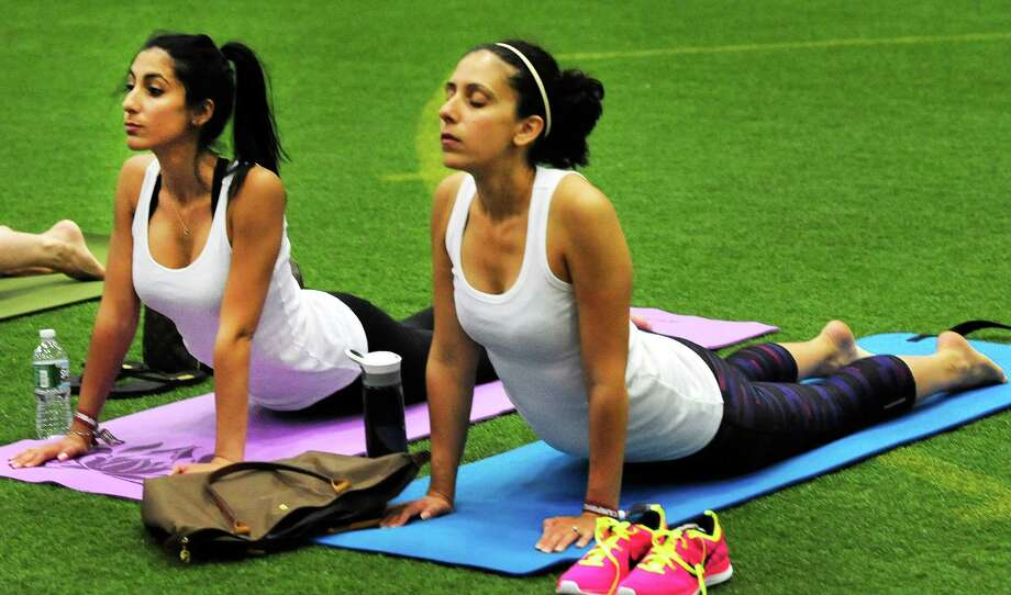 Sondra Alagna, left, and Christine Arconti, practice yoga at the Newtown Yoga Festival sponsored by Sandy Hook Promise, at the Newtown Youth Academy Sports and Fitness Center, in Newtown, Conn. Saturday, Aug. 24, 2013. Photo: Michael Duffy / The News-Times