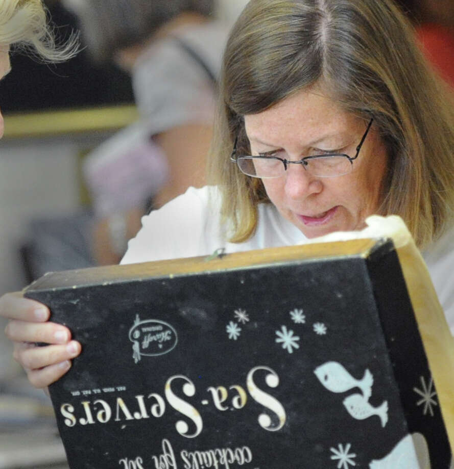 Greenwich resident Kathy Tosti inspects shrimp cocktail trays inside their original Franklin Simon & Co. store box during the Woman's Club of Greenwich annual philanthropic tag sale at the club in Greenwich, Saturday morning, August 24, 2013. Tosti said the Franklin Simon & Co. store was located where the Greenwich Library now stands. Club President, Trecie Fennell, said a good portion of the money raised from the sale will be used to fund scholarships awarded to Greenwich High School students headed to college. Photo: Bob Luckey / Greenwich Time
