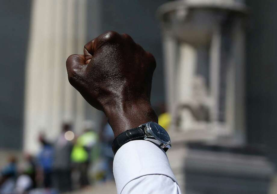 WASHINGTON, DC - AUGUST 24: A man raises his fist in the air while listening to speakers during the 50th anniversary of the March on Washington and Dr. Martin Luther King, Jr.'s 'I have a Dream' speech at the Lincol Memorial on August 24, 2013 in Washington, DC. The event included a commemorative march and rally along the historic route followed on August 28, 1963 and is being led by civil rights leader Al Sharpton and Martin Luther King III, King's oldest son. Photo: Mark Wilson, Getty Images / Getty Images