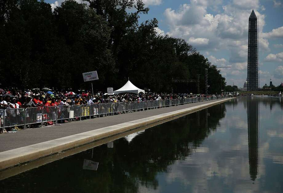 WASHINGTON, DC - AUGUST 24:  People gather at the Reflecting Pool to listen to speakers during the 50th anniversary of the March on Washington and Dr. Martin Luther King, Jr.'s 'I have a Dream' speech at the Lincol Memorial on August 24, 2013 in Washington, DC. The event included a commemorative march and rally along the historic route followed on August 28, 1963 and is being led by civil rights leader Al Sharpton and Martin Luther King III, King's oldest son. Photo: Mark Wilson, Getty Images / Getty Images