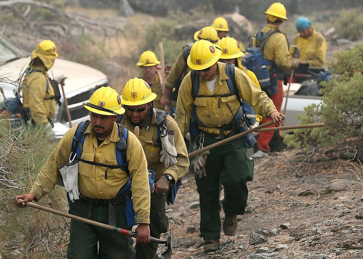Firefighters move in to douse a spot fire while battling the Rim Fire on Saturday in Yosemite National Park.