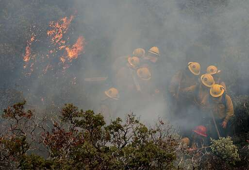 YOSEMITE NATIONAL PARK, CA - AUGUST 24: Firefighters move away from a burning manzanita bush as they battle the Rim Fire on August 24, 2013 in Yosemite National Park, California. The Rim Fire continues to burn out of control and threatens 4,500 homes outside of Yosemite National Park. Over 2,000 firefighters are battling the blaze that has entered a section of Yosemite National Park and is currently 5 percent contained. (Photo by Justin Sullivan/Getty Images) Photo: Justin Sullivan, Getty Images