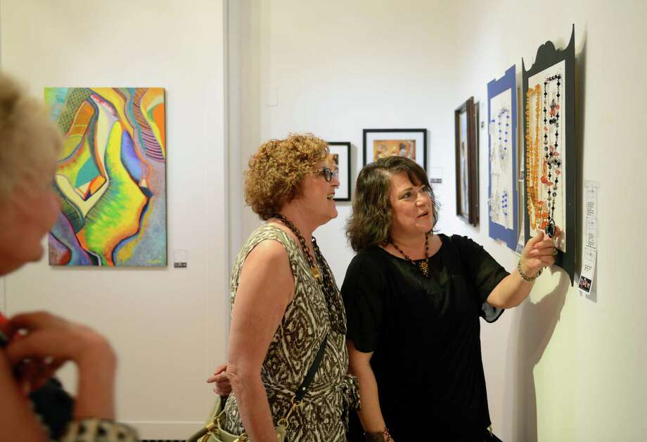 "Michele Goodman, left, of Ridgefield, chats with artist Lynne Boehm, of Out of the Box Jewelry in Redding, about one of her necklaces at the ""Bedlam"" gallery exhibition reception at the Ridgefield Guild of Artists in Ridgefield, Conn. on Saturday, Aug. 24, 2013.  The show gave members full control of the show, allowing them to hang up to two pieces of their work anywhere in the gallery on a first-come, first-serve basis.  The exhibit will be on display from Aug. 24 through Sept. 11, followed by the 36th Annual Juried Exhibition opening Sept. 28. Photo: Tyler Sizemore / The News-Times"