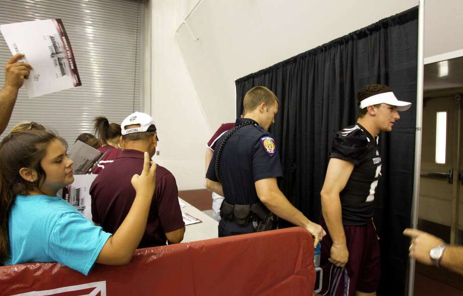 "Texas A&M quarterback Johnny Manziel is escorted away from his table at the end of ""Meet the Aggies."" Photo: Brett Coomer, Houston Chronicle / © 2013 Houston Chronicle"