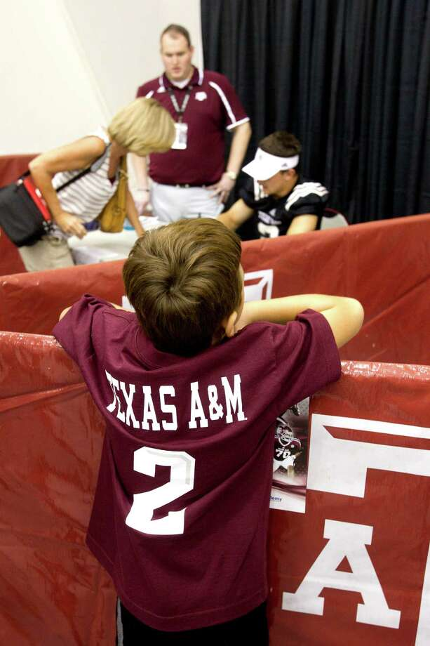 "Texas A&M fan Carsyn Roland, 9, peers over a barrier to take a look at quarterback Johnny Manziel during the ""Meet the Aggies"" event. Photo: Brett Coomer, Houston Chronicle / © 2013 Houston Chronicle"