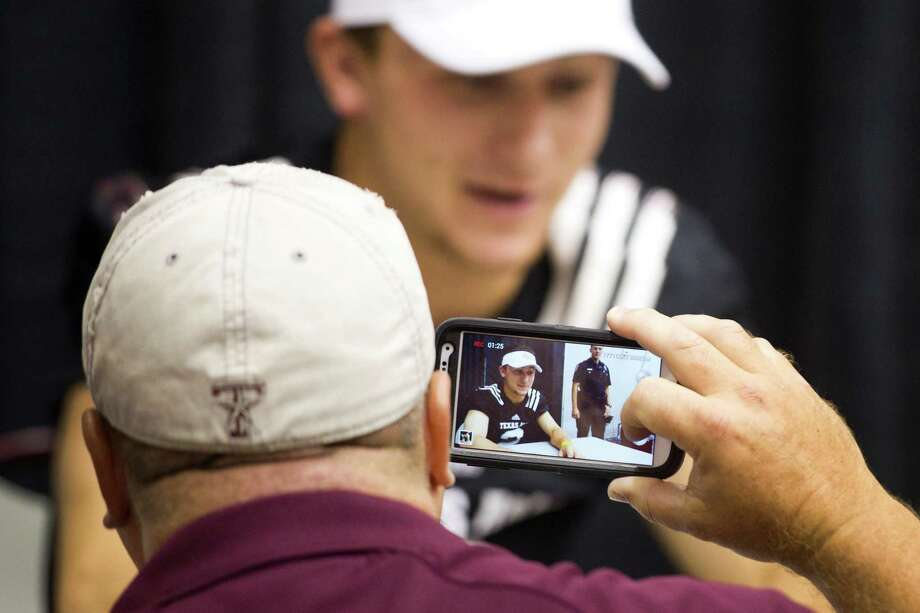 "Texas A&M quarterback Johnny Manziel is seen on the viewfinder of a smart phone as he signs autographs during the ""Meet the Aggies"" event. Photo: Brett Coomer, Houston Chronicle / © 2013 Houston Chronicle"