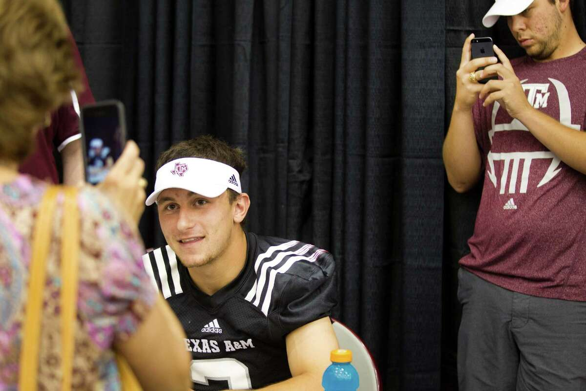 Texas A&M football fans take pictures of quarterback Johnny Manziel during the