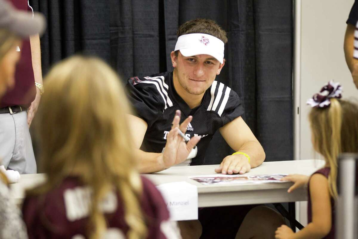 Texas A&M quarterback Johnny Manziel waves to fans as he signs autographs during the