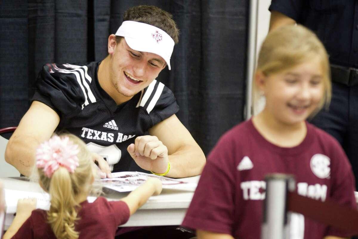Texas A&M quarterback Johnny Manziel signs autographs during the