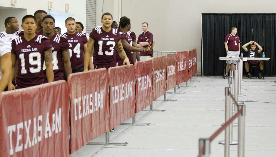 "Texas A&M football players arrive, with quarterback Johnny Manziel already seated, for ""Meet the Aggies."" Photo: Brett Coomer, Houston Chronicle / © 2013 Houston Chronicle"