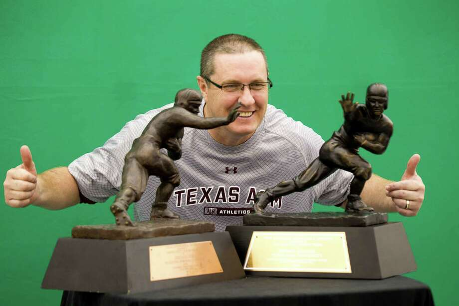 Texas A&M fan Thomas Cocks of College Station poses for a photo with a pair of Heisman trophies. Photo: Brett Coomer, Houston Chronicle / © 2013 Houston Chronicle