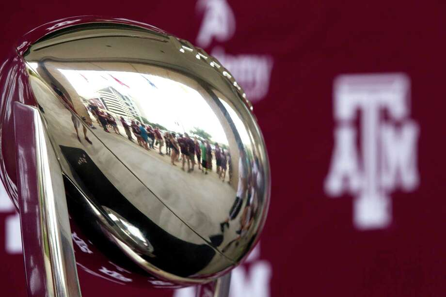 "Texas A&M fans are reflected in the Cotton Bowl trophy as they line up for the ""Meet the Aggies"" event. Photo: Brett Coomer, Houston Chronicle / © 2013 Houston Chronicle"