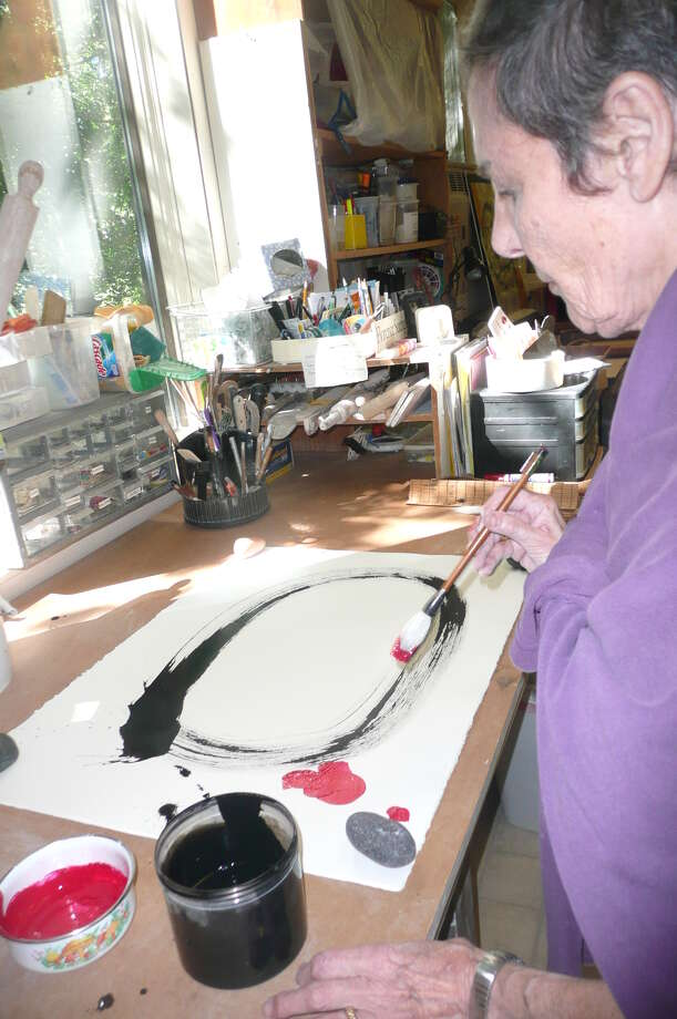 Suerig adds a touch of red ink to her Japanese calligraphy.  I learned calligraphy as a way of centering,  she says,  I ve been doing Ensō   Japanese circles. It s very meditative. Photo: Greenwich Time