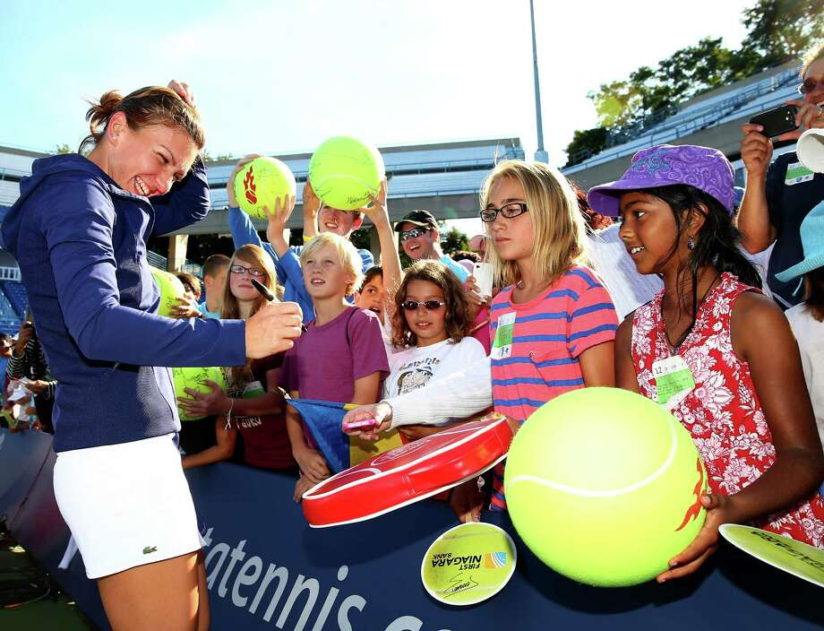 NEW HAVEN, CT - AUGUST 24:  Simona Halep of Romania signs autographs for fans after the Women's Final on Day Seven of the New Haven Open at Yale at the Connecticut Tennis Center on August 24, 2013 in New Haven, Connecticut. Halep defeated  Petra Kvitova of the Czech Republic 6-2,6-2. Photo: Elsa, Getty Images / 2013 Getty Images
