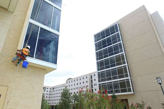 A window washer makes windows sparkle at the new Cougar Village II unit on the University of Houston campus.