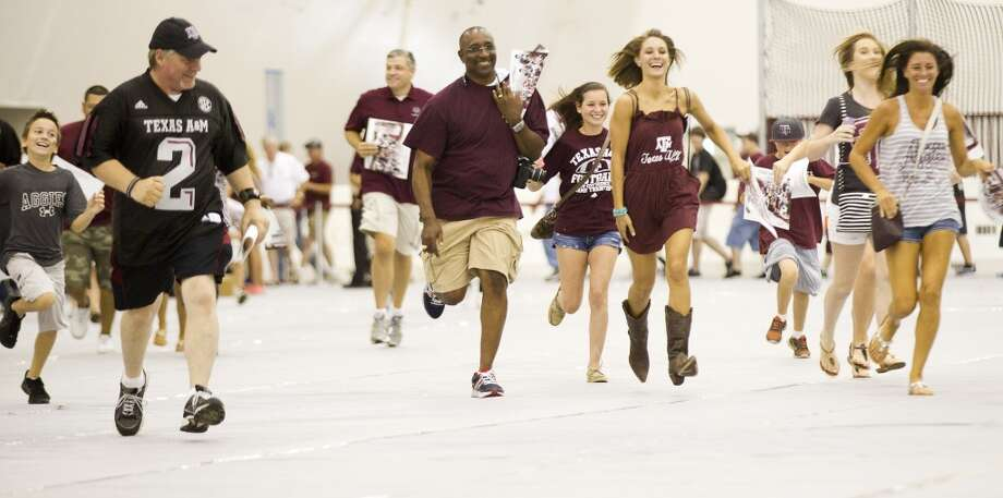 "Texas A&M fans run to get in line to get an autograph from quarterback Johnny Manziel during the ""Meet the Aggies"" event Saturday, Aug. 24, 2013, in College Station. Fans of the Texas A&M football team flocked to the Gilliam Indoor Track Complex to collect autographs and meet the Aggie players, one week prior to the team's season opener against Rice. ( Brett Coomer / Houston Chronicle ) Photo: Brett Coomer, Houston Chronicle"