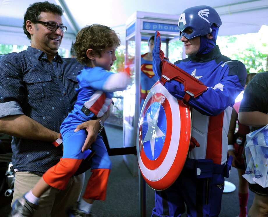 Angel Calva, of Norwalk, holds up his 4-year-old son Giorgio so he can high five another Captain America during ComiCONN at the Marriot Hotel in Trumbull, Conn. Saturday, Aug. 24, 2013. Photo: Autumn Driscoll / Connecticut Post