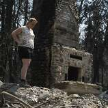 Corinna Loh gets her first look at the remains of a 4-bedroom home at her family's Spinning Wheel Ranch resort in Tuolumne County on Saturday, Aug. 24, 2013. The Rim Fire blazed through the property earlier in the week, destroying the home Loh grew up in, which was among several vacation rental homes on the property, as well as a 2-bedroom cabin.