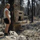 Corinna Loh views the remains of a 4-bedroom home at her family's Spinning Wheel Ranch resort in Tuolumne County on Saturday, Aug. 24, 2013. The Rim Fire blazed through the property earlier in the week, destroying the home Loh grew up in, which was among several vacation rental homes on the property, as well as a 2-bedroom cabin.