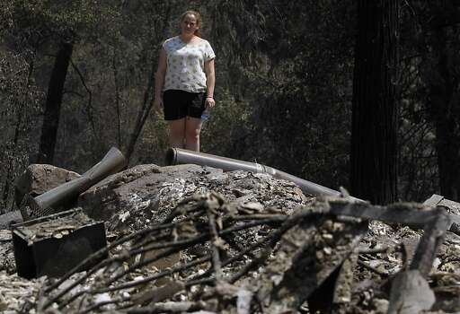 Corinna Loh views the remains of a 4-bedroom home at her family's Spinning Wheel Ranch resort in Tuolumne County on Saturday, Aug. 24, 2013. The Rim Fire blazed through the property earlier in the week, destroying the home Loh grew up in, which was among several vacation rental homes on the property, as well as a 2-bedroom cabin. Photo: Paul Chinn, The Chronicle