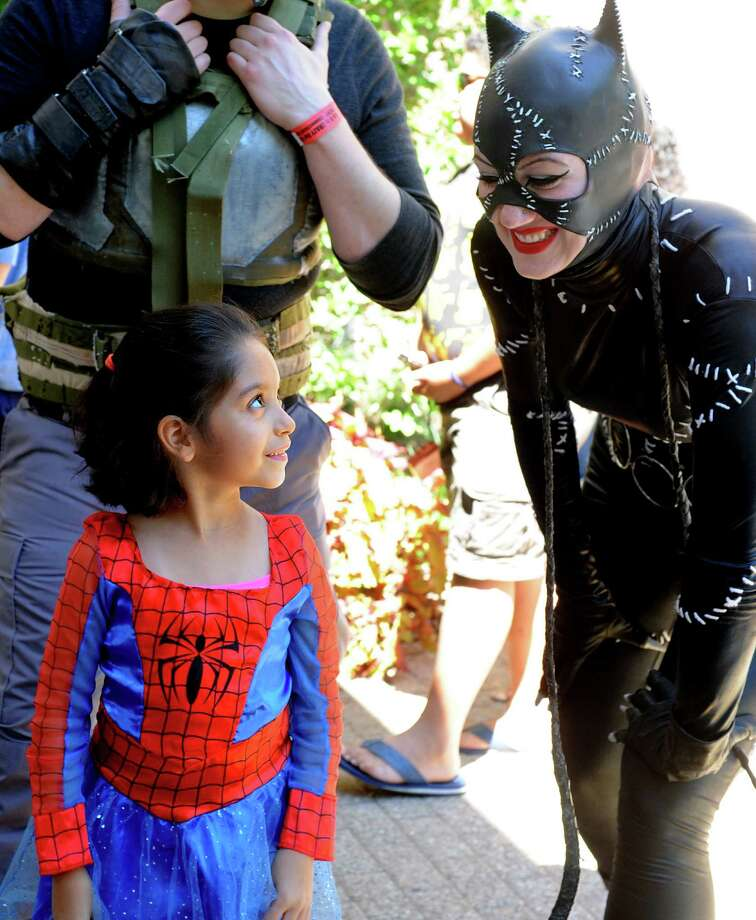 Seven-year-old Marissa Gonzalez, of Bridgeport, looks up at Catwoman Saturday, Aug. 24, 2013 during ComiCONN at the Marriot Hotel in Trumbull, Conn. Photo: Autumn Driscoll / Connecticut Post