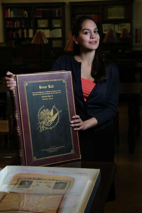 Mikaela Garza Selley, a Houston Public Library archivist whose duty is to oversee Hispanic materials, was excited to discover a leather-bound honor roll of Hispanic World War II veterans in the archives. Photo: Mayra Beltran, Staff / © 2013 Houston Chronicle
