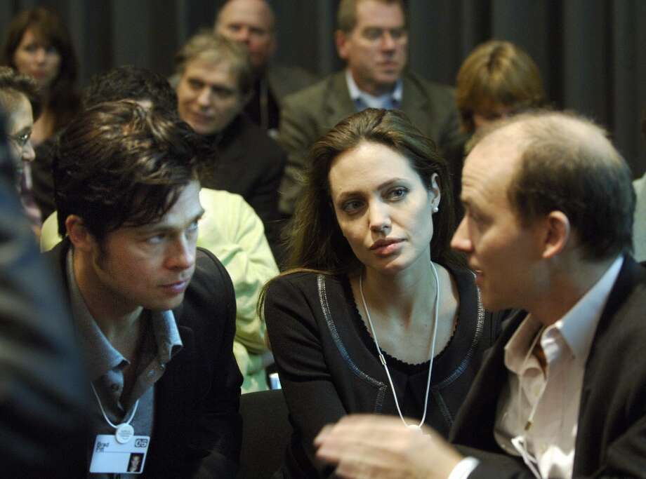"DAVOS, SWITZERLAND:  Actors Brad Pitt (L) and Angelina Jolie listen to an unidentified man while sitting with the audience at the session ""Next steps for Africa"" at the World Economic Forum in Davos 27 January 2006.     AFP PHOTO ERIC FEFERBERG  (Photo credit should read Eric FEFERBERG/AFP/Getty Images) Photo: ERIC FEFERBERG, AFP/Getty Images"