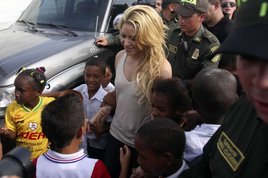 "Shakira greets children as she arrives to put the foundation stone for the construction of a school in Cartagena de Indias, Colombia, on April 11, 2011. The project, led by Shakira's Foundation ""Barefoot"", will have a capacity to house about 1,500 students. AFP PHOTO/STR (Photo credit should read STR/AFP/Getty Images) Photo: STR, AFP/Getty Images"